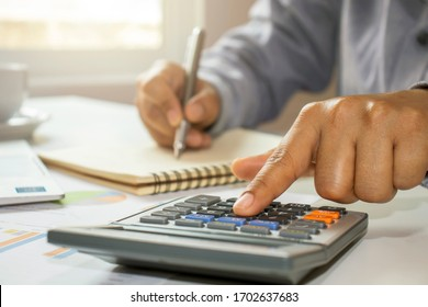 Close-up of women using calculators and note-taking, accounting reports, cost-calculation ideas, and saving money.