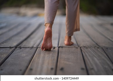 Closeup of a women's bare feet walking at a wood walk way at sunset, with a blur background nature