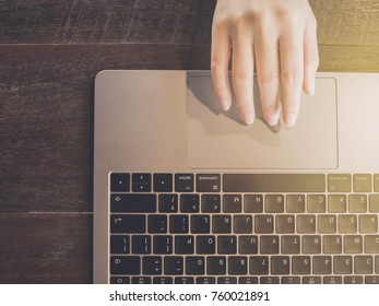 Closeup of women's hand is business working by touching laptop keyboard on wood table in coffee cafe