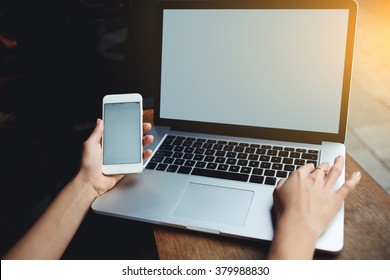Closeup of women's hands using mobile phone and laptop computer with blank copy space screen for your advertising text message or content, female holding cell phone and keyboarding on net-book