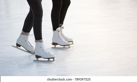 close-up of women's legs on skates in winter on an open skating rink, place for text/ The ice skates of two friends skating together on a winter afternoon/ Winter time, outdoor activities  - concept