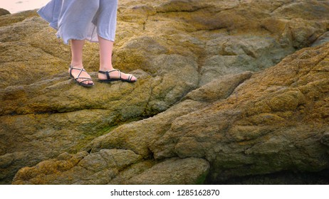 c5a1ec43c9d132 close-up. women s legs in sandals and a long gray skirt are on the