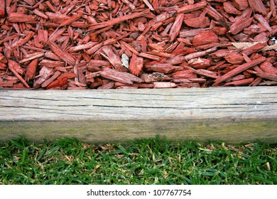 Closeup of wood chip on garden with wooden border and green grass