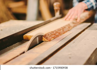 Closeup of wood cutting table with electric circular saw. Man skilled cabinet maker using circular saw at woodworking workshop. Professional carpenter cutting wooden board at sawmill. Sawing machine