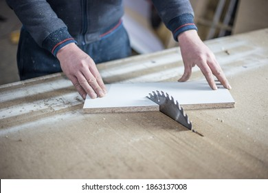 Closeup of wood cutting table with electric circular saw. Professional carpenter cutting wooden board at sawmill
