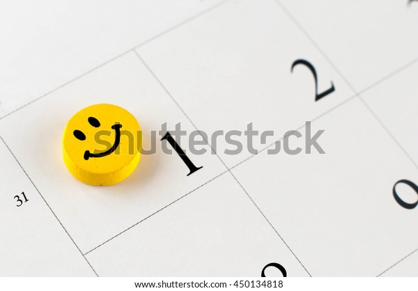 Closeup of wooden bead with drawing happy emotion on the calendar page; small depth of field.