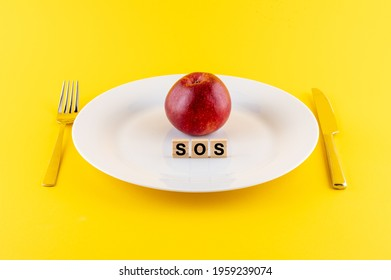 A closeup of wooden blocks with SOS phrase and an apple on a white plate with a knife and fork