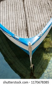 Close-up of a wooden blue and white prow of a rowing boat moored in a port. Liguria, Italy