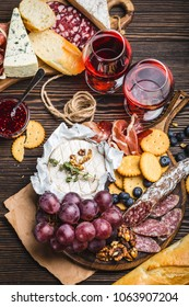 Close-up of wooden boards with cold meat, variety of cheese, fruit, bread and glasses of red wine. Wooden background. Delicatessen plate. Mix of different snacks/appetizers. Close-up. Delicacy platter