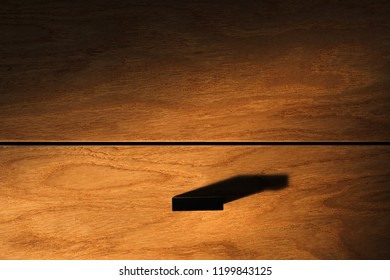 Closeup of a wooden cabinet drawer dramatically lit by direct afternoon window light.