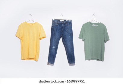 Closeup of Wooden Clothes hanger with green and yellow cotton t-shirt and blue jeans on white background.