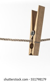 Close-up of wooden clothespins hanging on the rope