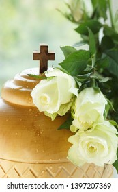 closeup of wooden cremation urn covered with white roses and water drops