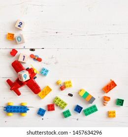Gros plan sur des cubes en bois avec les chiffres 2018, 2019 année. Vue de dessus sur des jouets éducatifs pour enfants, des cubes multicolores, des briques et d'autres détails sur fond blanc bois.