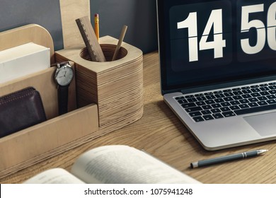 Close-up of wooden desk organizer with pencil and watch, computer, pen and book lying on the desk