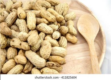 Closeup wooden dish of Peanut, Ground nut, Earth nut, Goober nut, Pindar nut, Monkey nut on white background; Top view of Peanut, Ground nut, Earth nut, Goober nut, Pindar nut, Monkey nut.