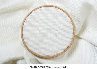 Closeup of wooden embroidery hoop and clean white fabric for hobby needlework.Empty space for design. Template for hobby design