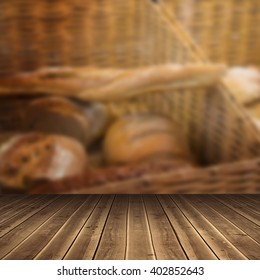 Close-up of wooden flooring against baskets with breads freshly baked and tongs