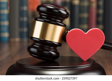 Close-up Of Wooden Gavel And Red Heart On Table