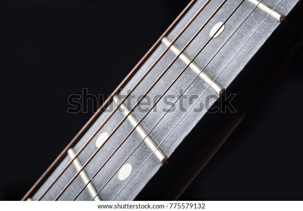 Close-up of wooden guitar neck with fretboard and tensioned strings.
