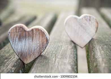 closeup of wooden hearts on bench in outdoor - Love concept