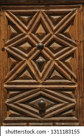 Close-up of wooden old door with geometric decoration carved on the surface, in a sunny day at Avila. It has the longest and imposing wall completely encircling this well-kept gothic town in Spain.