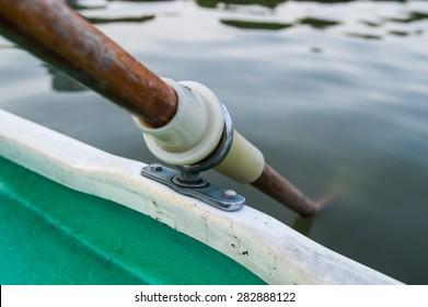 Closeup of wooden paddle locked on gunwale