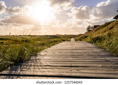 Closeup of wooden path heading along the coastline of Amrum Germany.