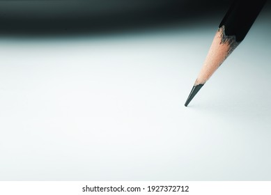 Close-up of a wooden pencil ready to be drawn on white paper. In the image, the paper is still blank to fill in, insert or create a plan for doing something.