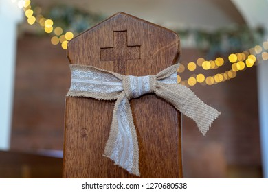 closeup of wooden pew in church with bow on it and ferry lights blurred in the background
