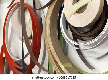 Closeup of wooden and plastic edge banding tapes at carpenter's workshop