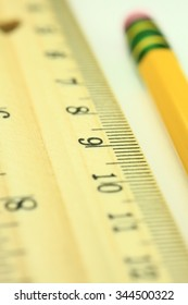 Closeup of wooden ruler with yellow pencil.