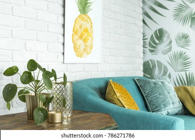 Close Up Of Wooden Table With Plant, Vase And Candle Next To Blue Couch