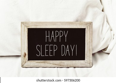 closeup of a wooden-framed chalkboard with the text happy sleep day written in it, placed on a comfortable bed
