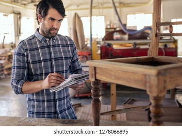 Closeup of woodworker standing by a chair on a workbench in his carpentry workshop reading over designs in a notebook