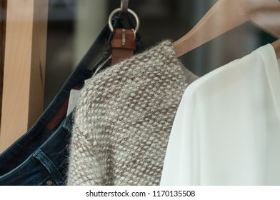 closeup of wool pullover on hangers in a woman fashion store showroom