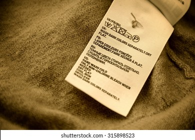 Close-up of woolen product wash warning tag in multiple languages.