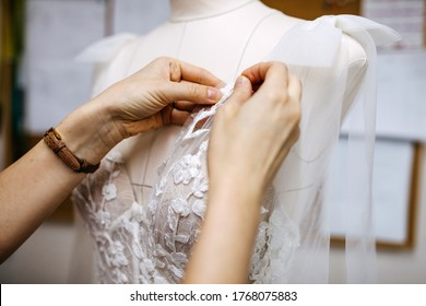 Close-up of work process of a tailor in her studio. Hands sewing bridal dress process, pinning lace on mannequin.