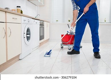 Close-up Of Worker Cleaning Floor With Mop In Kitchen Room