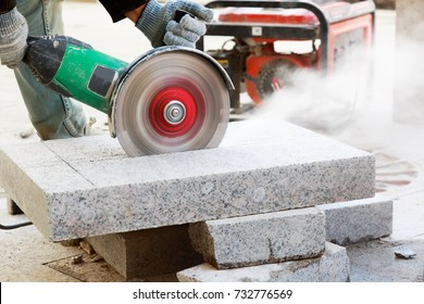 Close-up of worker cutting granite slab with grinder. Dust while grinding stone pavement