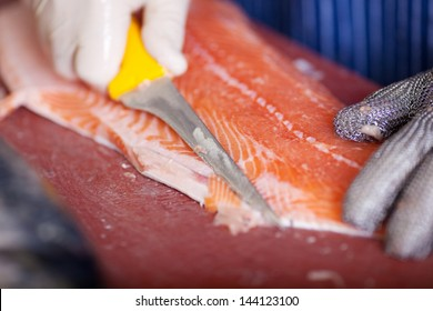close-up of worker cutting salmon fillets with a knife