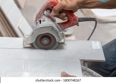 Closeup of worker cutting a white tile with blade for assembly, copy space