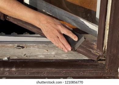 Closeup of worker hand sanding old wooden window using sanding sponge
