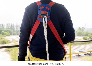 Close-up worker in safety harness on high construction site . Concept for occupational health safety in construction.