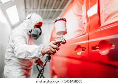 Nahaufnahme eines Arbeiters mit Sprühpistole und Airbrush und Anstrich eines roten Autos