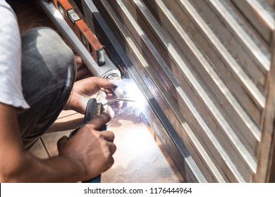 Closeup of worker welding auto gate arm onto new metal gate