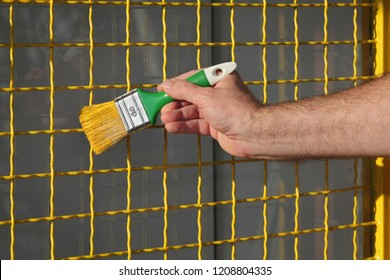 Closeup of workers hand painting metal security window netting to yellow color