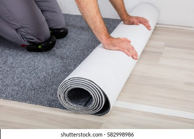 Close-up Of Worker's Hands Unrolling Carpet On Floor At Home