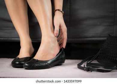 Closeup of a working woman hand taking off her too tight and narrow shoes after suffering for a long day pain and sore - Medical condition called bunions, Hallux valgus, Woman's Health - feet problem.