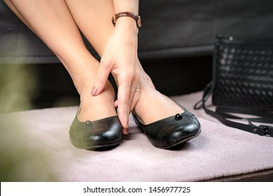 Closeup of a working woman hand touching her bunion feet after suffering for a long day pain and sore - Medical condition called bunions, Hallux valgus, Woman's Health - feet problem.